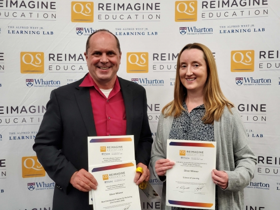 Image of instructors Chris Caplice and Mary Ellen Wiltrout accepting awards